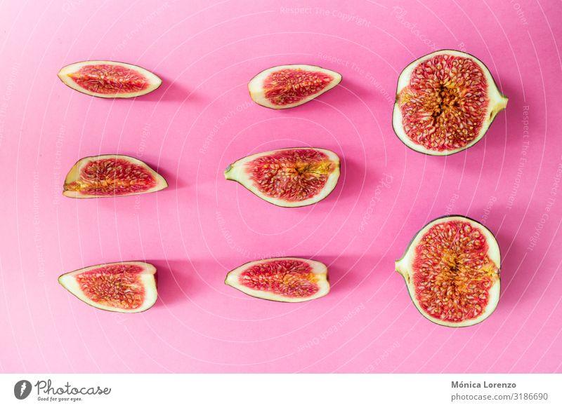 Reife Feigen auf rosa Hintergrund geschnitten. Minimale flache Verlegung. Frucht Ernährung Diät exotisch Herbst frisch rot roh Hälfte Jahreszeiten süß Scheibe
