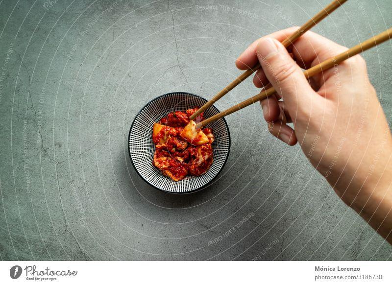 Die Hand des Mannes benutzt Essstäbchen, um Kimchi zu nehmen. Koreanische Küche. Gemüse Ernährung Mittagessen Abendessen Vegetarische Ernährung Asiatische Küche