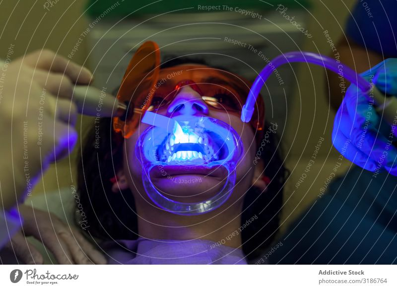 Stomatologenhände machen Ultraschall für Patientenzähne mit Spezialwerkzeugen deutlich. Zahnarzt Füllung regenarm Prüfung & Examen Geselle Gerät dental