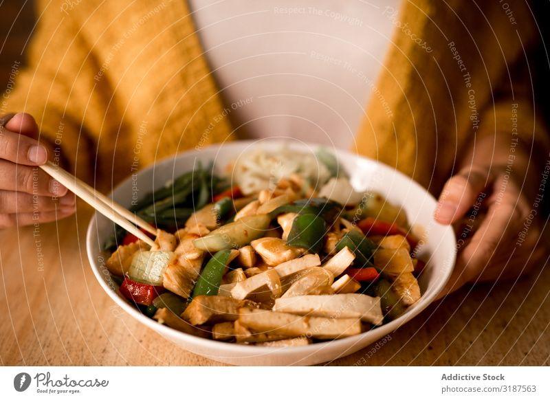 Weibliche Essschüssel mit gekochtem, appetitanregendem Diätgericht Lebensmittel Vegetarische Ernährung Gemüse Möhre Zwiebel Paprika Pilz Essstäbchen