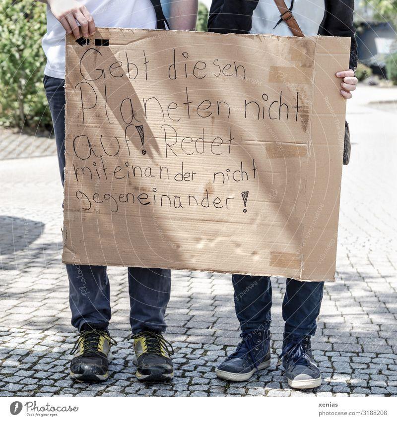 Weltschmerz / zwei Jugendliche stehen auf der Straße und halten beschrifteten Karton in den Händen für fridays for future - Demonstration - Gebt diesen Planeten nicht auf! Redet miteinander nicht gegeneinander!