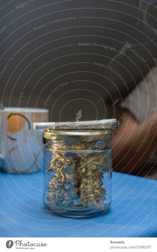 Ein Glasgefäß voller Cannabisknospen und einem Marihuana Joint. Heißgetränk Kaffee Espresso Topf Lifestyle Gesundheitswesen Behandlung Alternativmedizin Rauchen