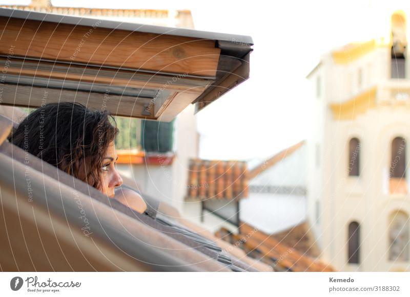 Junge Frau, die die Stadt aus dem Fenster eines Dachgeschosses betrachtet. Lifestyle schön Wellness harmonisch Erholung Meditation Ferien & Urlaub & Reisen