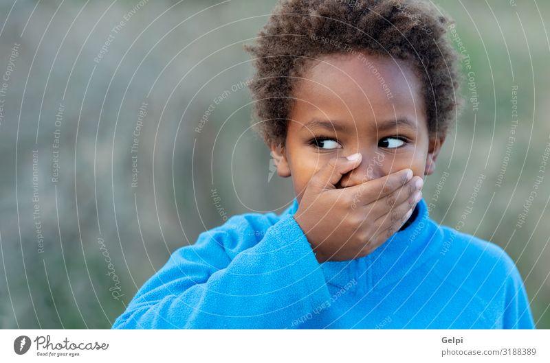 Kleiner afrikanischer Junge, der seinen Mund mit einem blauen Trikot bedeckt Glück schön Gesicht Windstille Kind Schulkind Mensch Mann Erwachsene Kindheit