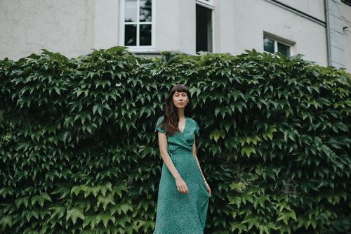 Frau in einem eleganten grünen Kleid steht vor einer Hecke Erwachsener attraktiv schöne Frau charmant schick Großstadt klassisch Bekleidung selbstbewusst Europa