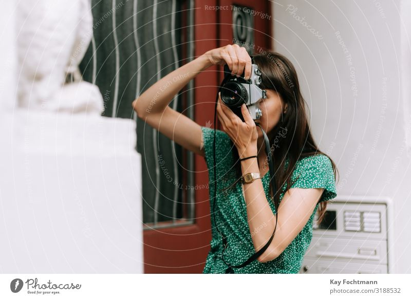 elegante Frau in grünem Kleid macht ein Foto mit einer alten Filmkamera Aktivität analog Schönheit Fotokamera erfassend Kaukasier entdeckend Eleganz Europäer