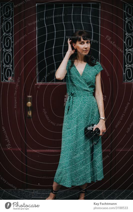 elegante Frau in grünem Kleid hält eine alte Filmkamera in den Händen Aktivität analog Schönheit Fotokamera erfassend Kaukasier entdeckend Eleganz Europäer