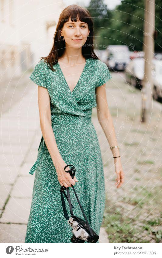 elegante Frau in grünem Kleid geht mit einer alten Filmkamera in der Hand Aktivität analog Schönheit Fotokamera erfassend Kaukasier entdeckend Europäer erkunden