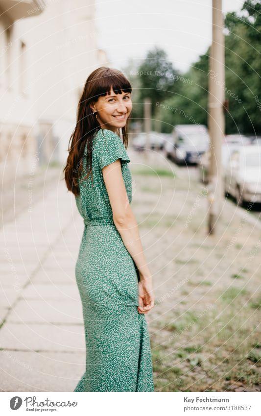 Eine Frau in einem eleganten grünen Kleid dreht sich um und lächelt in die Kamera Erwachsener attraktiv schöne Frau charmant schick Großstadt klassisch