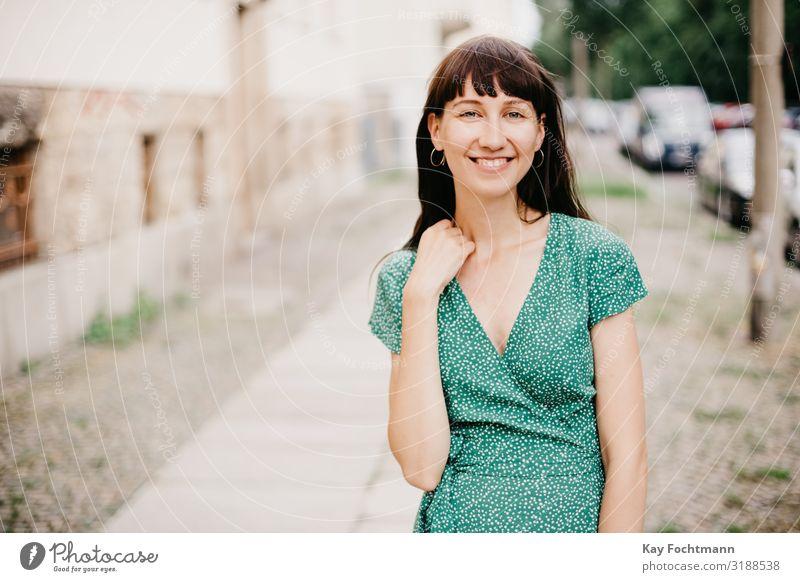 Eine Frau in einem eleganten grünen Kleid lächelt in die Kamera Erwachsener attraktiv schöne Frau charmant schick Großstadt klassisch Bekleidung selbstbewusst