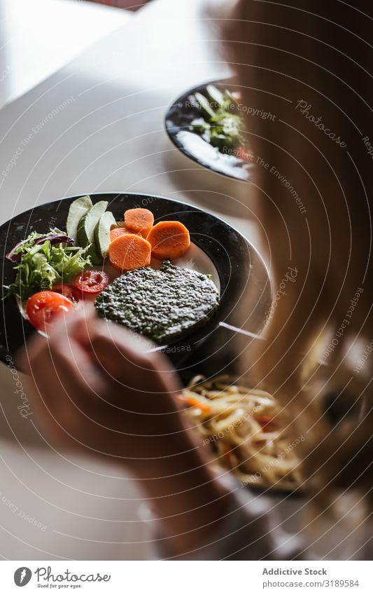 Anonymes Mädchen, das zu Hause vegane Speisen isst. Egoperspektive Kind Vegane Ernährung Lebensmittel Essen Nudeln Küche heimwärts sitzen Tisch Zusammensein