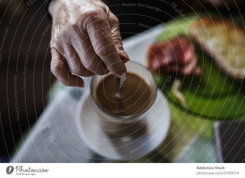 Hand der alten Frau, die den Löffel in der Tasse hält. rühren Kaffee trinken Frühstück Getränk heiß Lebensmittel Morgen Mensch Senior Tisch aromatisch Koffein