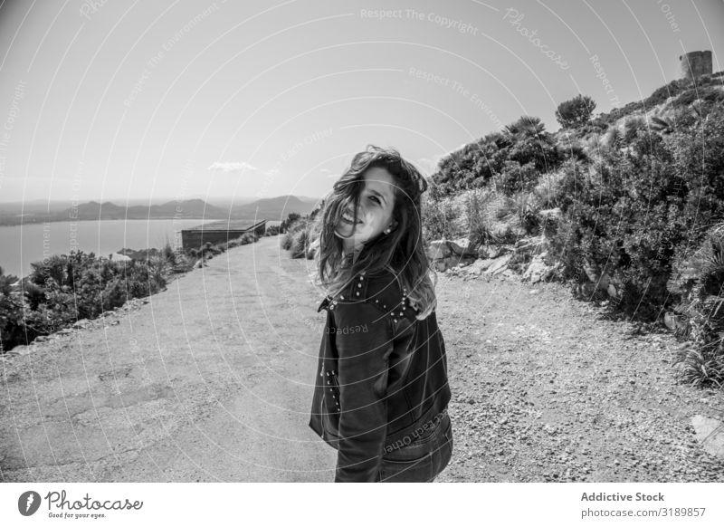 Lächelnde Frau an der Küste Meer Lifestyle Freizeit & Hobby Sonnenstrahlen Tag lässig Jugendliche Erholung Freude froh Vergnügen heiter Natur Landschaft Dame