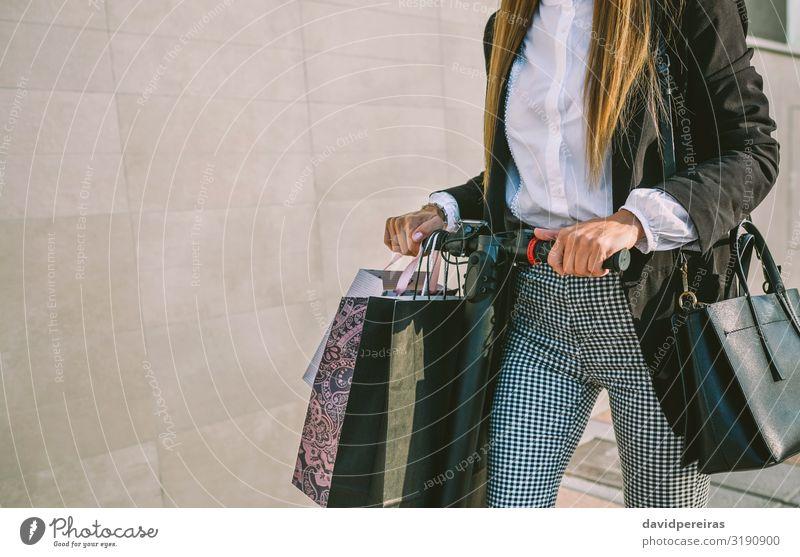 Unkenntliche Frau mit Einkaufstaschen auf Elektroroller kaufen elegant Stil Mensch Erwachsene Hand Verkehr Straße Mode Hemd blond modern Schwarzer Freitag