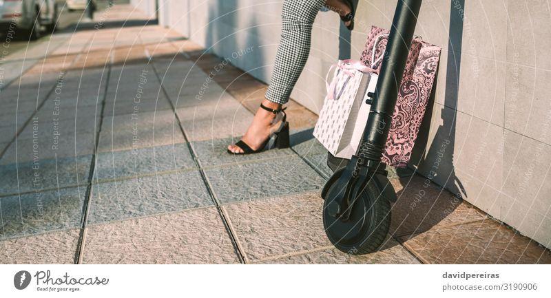 Elektroroller mit Einkaufstaschen und Frau im Hintergrund. kaufen elegant Stil Internet Mensch Erwachsene Fuß Verkehr Straße Mode modern Rad ökologisch Öko