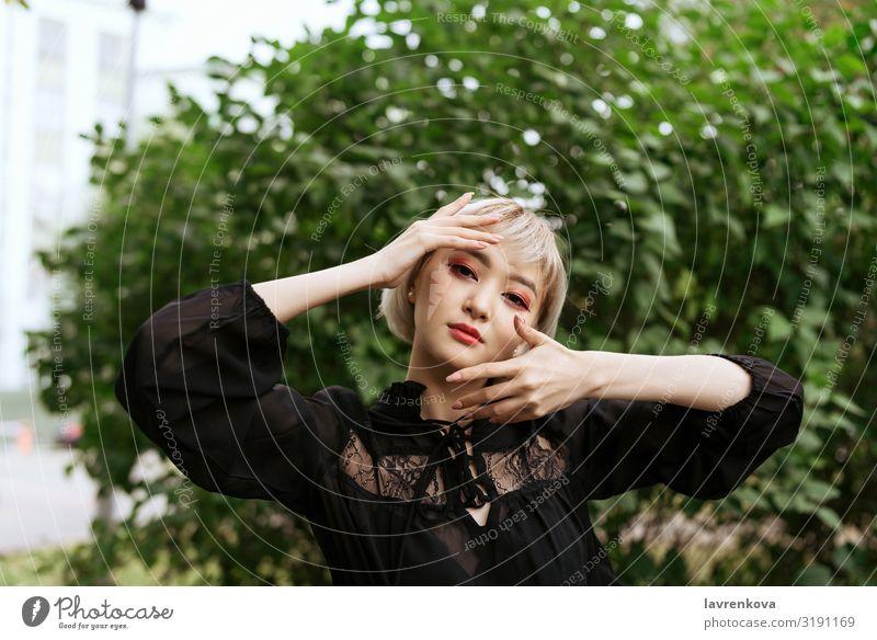 asiatische Frau, die ihre Hände um ihren Kopf hält oben ringsherum Asiate blond Nahaufnahme niedlich Auge Gesicht gestikulieren Junge Frau Hand kawaii Blatt