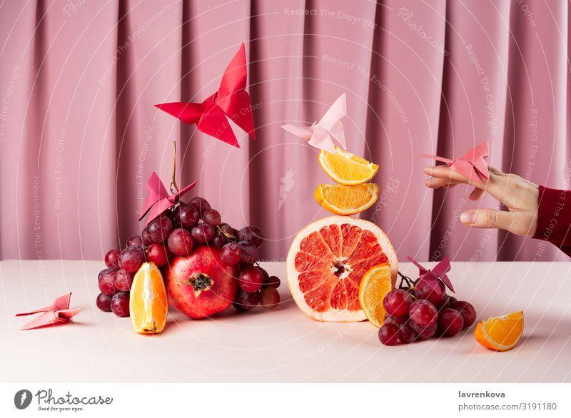 Verschiedene Früchte auf rosa Tisch mit Origame-Papier-Schmetterlingen Frühstück Zitrone Zitrusfrüchte Diät Lebensmittel Gesunde Ernährung Foodfotografie frisch