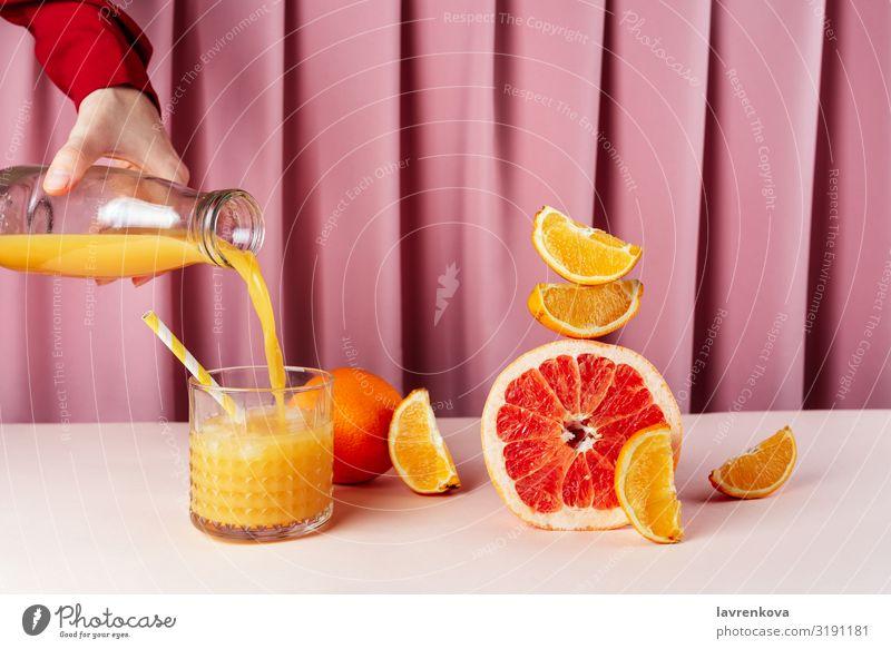 Frau, die Saft in die Tasse auf dem Tisch mit Zitrusfrüchten gießt. Getränk Frühstück Zirkus Zitrone Cocktail Diät trinken Lebensmittel Gesunde Ernährung