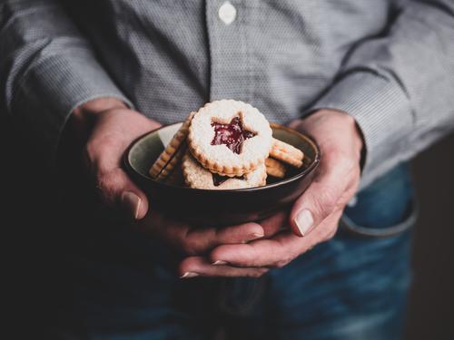 Mann hält Weihnachtskekse in einer Schüssel in seinen Händen Lebensmittel Teigwaren Backwaren Keks Weihnachtsgebäck Kaffeetrinken Schalen & Schüsseln Lifestyle