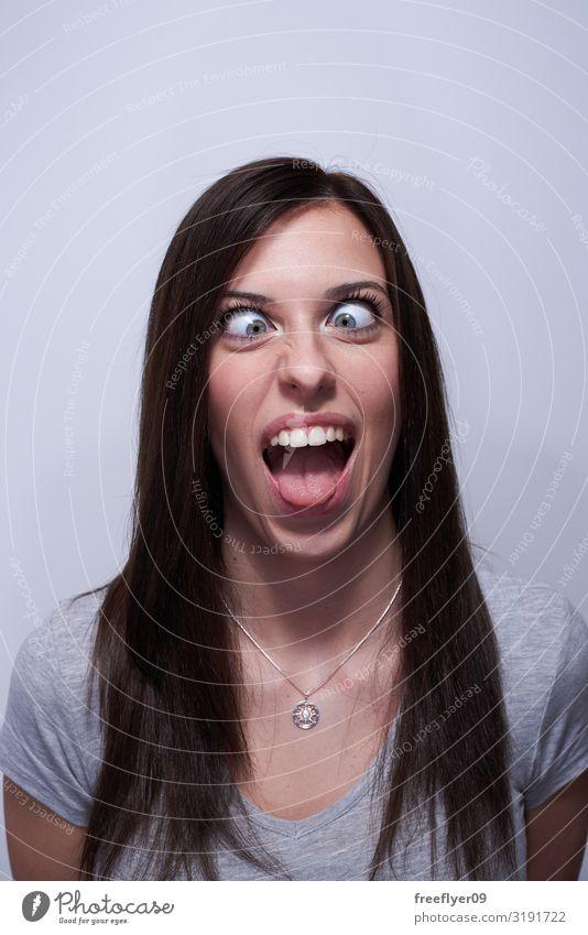 Porträt einer Frau mit gekreuzten Augen, die alberne Gesichter macht. Freude schön Mensch Erwachsene T-Shirt brünett langhaarig lachen lustig blau grau weiß