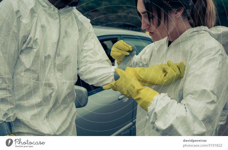 Frau klebt einem Mann bakteriologische Schutzhandschuhe an Medikament Arbeit & Erwerbstätigkeit Mensch Erwachsene PKW Handschuhe Sicherheit Krise Seuche klebend