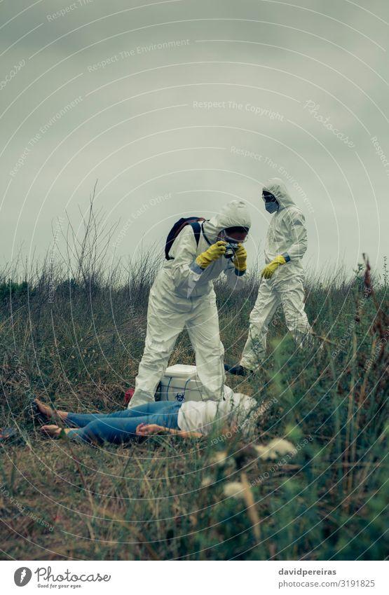 Mann und Frau im Schutzanzug beim Fotografieren einer Leiche Körper Fotokamera Mensch Erwachsene Tod gefährlich nehmen Grafik u. Illustration Seuche Virus