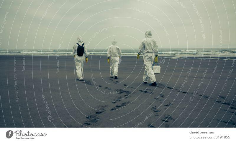 Menschen mit Schutzanzügen, die am Strand spazieren gehen. Meer Wellen Frau Erwachsene Mann Sand Küste Handschuhe Fußspur Krise unkenntlich laufen