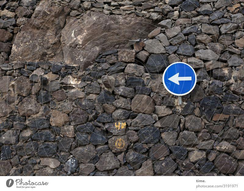 Richtungsvorschlag stein mauer schild verkehrszeichen steine dunkel braun blau links richtung orientierung tageslicht ordnung pfeil