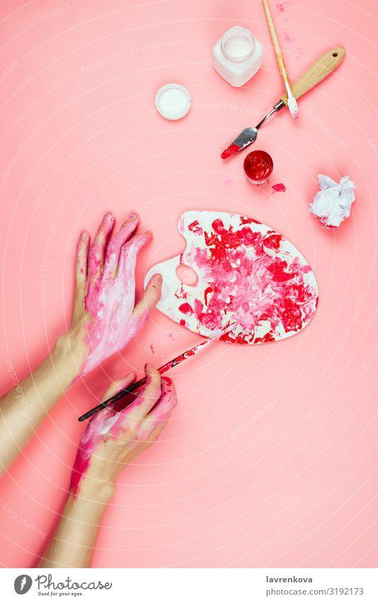 Frauenhände mit Farbe bedeckt und Künstlerbedarf auf rosa Zeichnung Design Erwachsene Körper Bürste Entwurf Kreativität Gemälde Finger Junge Frau Gouachefarbe
