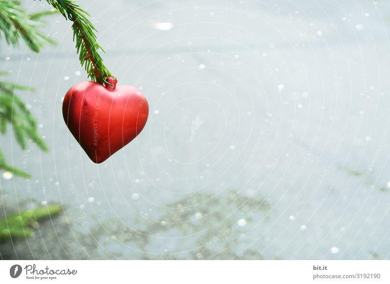 Roter Christbaumanhänger in Herzform, hängt an grünem Tannenzweig im leichtem Schneefall, vor hellem, grauen Hintergrund. Weihnachtsdekoration trostlos, spärlich, wiederverwertet. Trister, kaputter, alter Weihnachtsbaum steht draussen im Müll auf Straße.