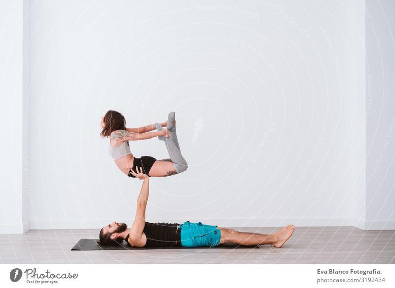 junges Paar, das in einem weißen Studio oder einer Sporthalle Akro-Yoga praktiziert. Gesunder Lebensstil Gesundheit Mann Kraft Mensch