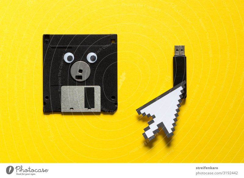 Eine ausgediente Diskette schaut mit wehmütigem Blick auf den USB-Stick, dem der Mauszeiger den Vorzug gibt Büroarbeit Medienbranche Computer Notebook