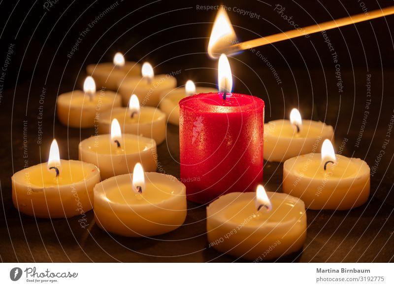 Ein Streichholz entzündet das Feuer vieler Kerzen Meditation Feste & Feiern Wärme Kirche Denkmal dunkel rot schwarz Hoffnung Trauer Tod Sehnsucht Frieden