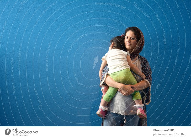 Muslimische Mutter umarmte das geschlafene kleine Mädchen vor der Wand. Lifestyle schön Leben Erholung Innenarchitektur Kind Mensch feminin Junge Frau