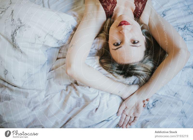 Frau, die zu Hause im Bett liegt. verführerisch Erotik lügen geöffneter Mund Jugendliche schön Schlafzimmer heimwärts Mensch aussruhen Glück heiß itim Lifestyle