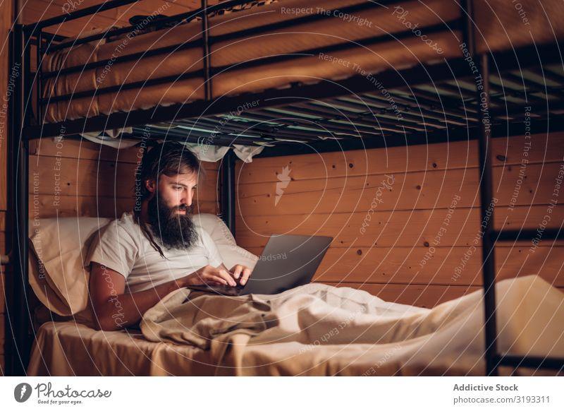 Mann mit Laptop im rustikalen Etagenbett Notebook benutzend Schickimicki Arbeit & Erwerbstätigkeit freiberuflich bärtig Holz Haus konzentriert
