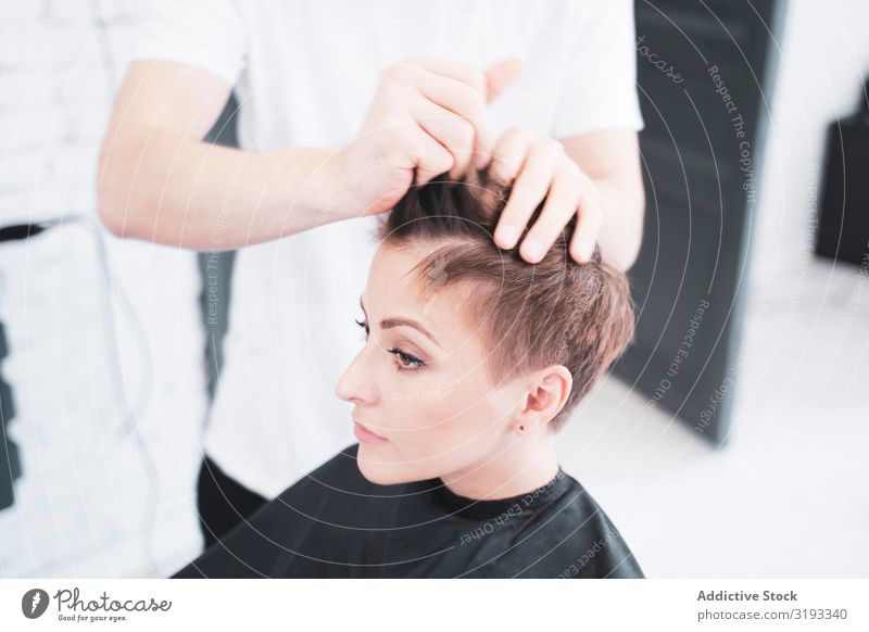 Friseur, der die Finger der Frau kämmt. Mann Kämmen Vollbart Salon Jugendliche schön Mädchen Friseursalon Behaarung Kunde Schickimicki Pflege Klient Fürsorge