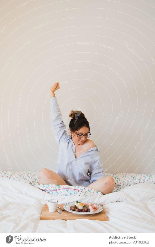 Junge Frau mit Frühstück auf dem Bett, die sich ausdehnt. Aufwachen strecken Gesundheit Lebensmittel Morgen Tablett Kaffee Grapefruit eingesteckt Ei sitzen