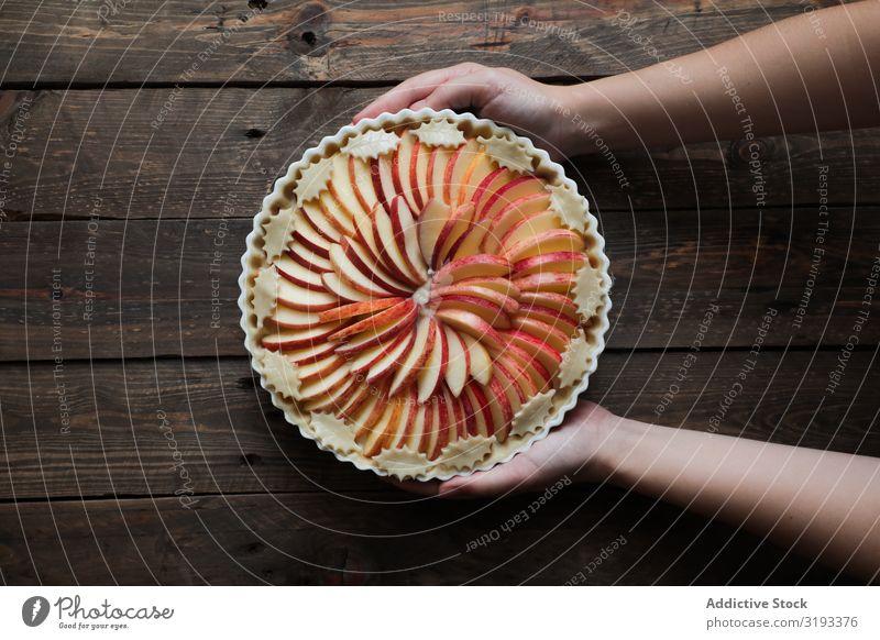 unkenntliche Frau, die einen leckeren Apfelkuchen auf einem Holztisch zeigt. Pasteten frisch rustikal Fenster gebastelt Tag braun Konfekt organisch Pergament