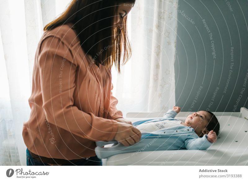 Frau, die ein bezauberndes kleines Baby anzieht. Mutter Dressing neugeboren Liebe Fürsorge Eltern Säuglingsalter Fröhlichkeit unschuldig Kind lieblich reizvoll
