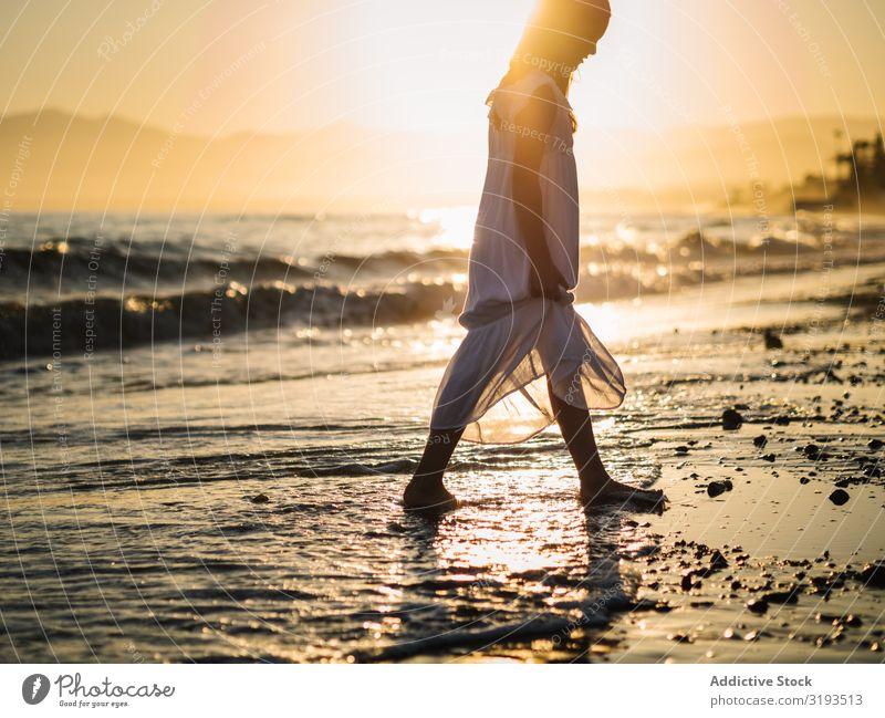 Liebenswertes Mädchen, das bei Sonnenuntergang am Meer spazieren geht. Seeküste laufen reizvoll Küste Strand Sommer Wasser Sonnenstrahlen Kind Kindheit Glück