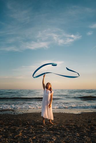 Liebenswertes Mädchen spielt mit dem Band am Meer. Spielen Seeküste reizvoll Schnur Küste rennen Abend Strand Spaß haben Sommer Wasser Kind Kindheit heiter