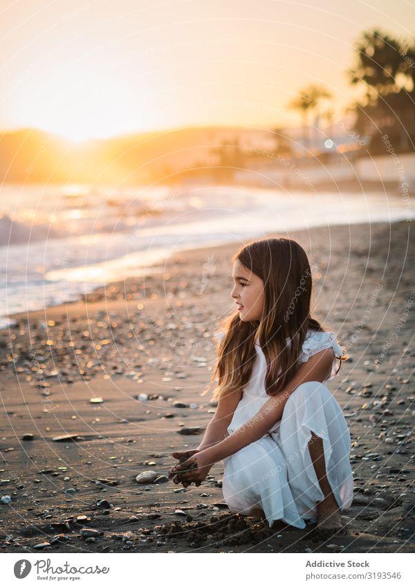 Liebenswertes Mädchen spielt mit Sand am Strand. Spielen reizvoll Seeküste Sonnenlicht niedlich Sonnenuntergang Kind Kindheit Porträt besinnlich träumen Küste