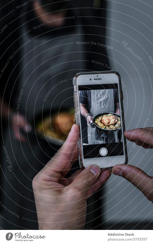 Fotograf, der Koch und Gericht fotografiert. Fotografie Speise Handy fotografierend Lebensmittel Tradition Abendessen gebastelt Restaurant Gesundheit