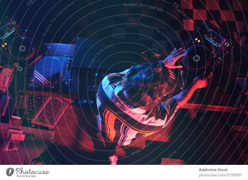 Von oben ein anonymer DJ-Mann, der in einem Club mit Licht spielt. Nachtclub Hand Entertainment Schallplatte Spielen Gerät Plattenteller Party Scheibe