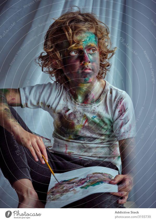 Süßer Junge verschmiert in Farben Zeichnung auf Papier bemalt beschmiert Gemälde Leinwand Freude spielerisch Kind Kreativität lustig dreckig niedlich hübsch