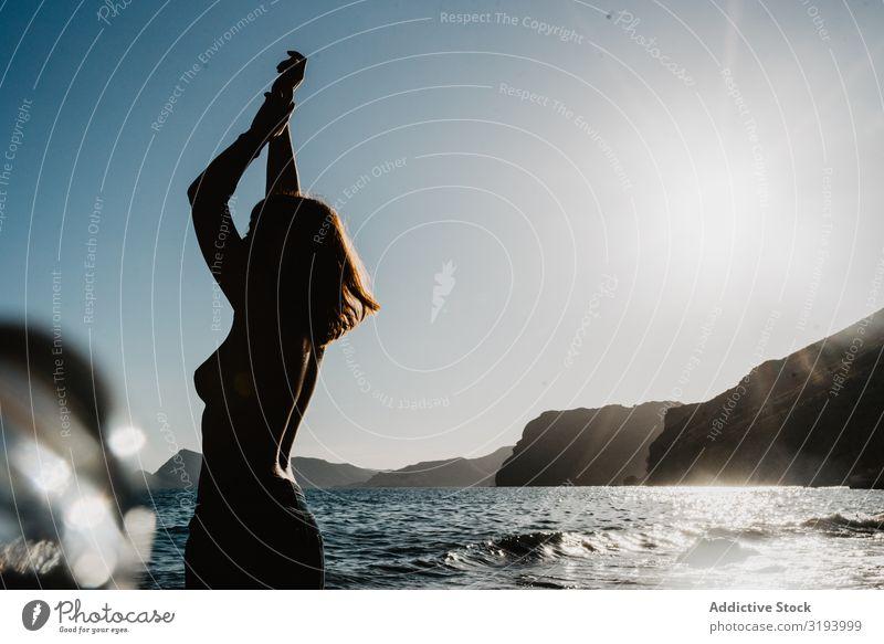 Oben ohne Frau, die auf dem wogenden Meer posiert. oben ohne Freiheit Wellen Küste tretend Unwetter Jugendliche Jeanshose ohne Hemd Strand Aufregung Schaum