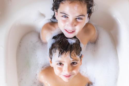 Zwei Kinder beim Baden, die eine Kamera sehen. Lifestyle Freude Glück schön Körperpflege Haut Wohlgefühl Schwimmen & Baden Badewanne Mensch Baby Kleinkind Junge