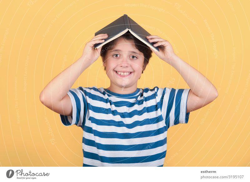 glückliches Kind mit Buch auf dem Kopf Lifestyle Freude Spielen lesen Schule lernen Schulkind Mensch maskulin Kindheit 1 8-13 Jahre Lächeln lachen Fröhlichkeit