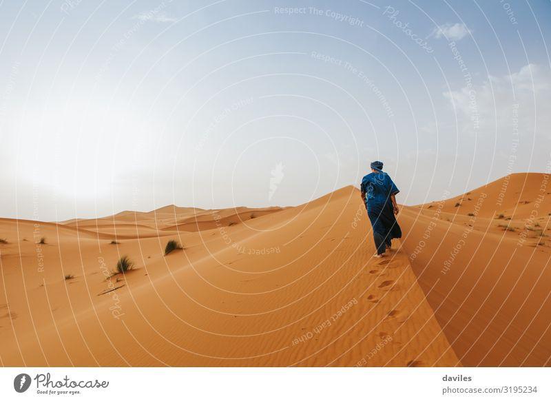 Ein arabischer Mann in blauer Kleidung läuft auf einer Wüstendüne. Lifestyle exotisch Ferien & Urlaub & Reisen Tourismus Ausflug Abenteuer Expedition Sonne